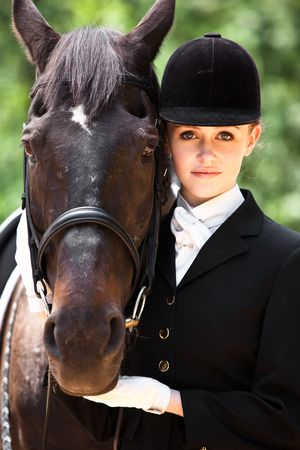 A caucasian girl getting ready for a horseback riding posing with her horse