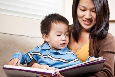 Photo pour A portrait of a mother and a son reading a book - image libre de droit