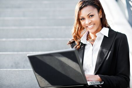 A shot of a beautiful black businesswoman working on her laptop outdoor