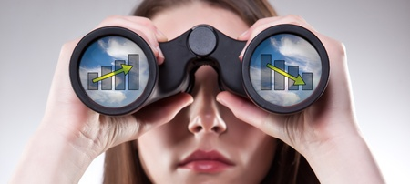 A businesswoman looking through binoculars, seeing conflicting trends in earnings prediction, can be used for business vision or business prediction concept