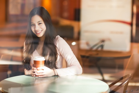 A shot of a beautiful asian woman drinking coffee in a cafe