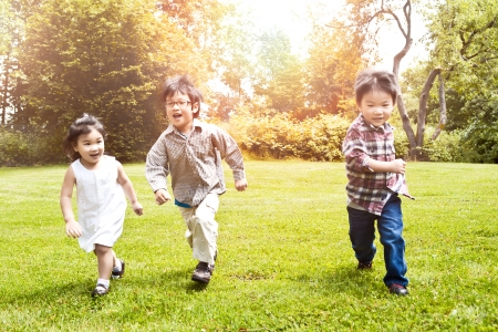 Photo pour A shot of three Asian kids running in a park (focus in the middle kid) - image libre de droit