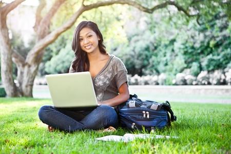 Foto de A shot of an Asian student working on laptop on campus - Imagen libre de derechos