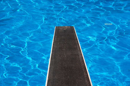 Swimming pool with diving board and reflections