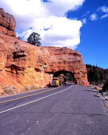 Large American truck driving under a rock arch, Red Canyon, Dixieland National Forest, Utah, USA