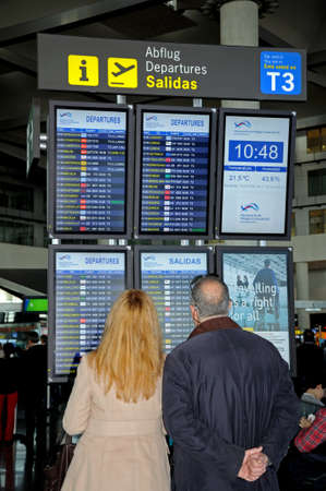 Malaga, Spain - January 29, 2012 - Passengers looking at departure destination boards in Terminal 3, Malaga airport, Malaga, Malaga Province, Costa del Sol, Andalucia, Spain, Western Europe