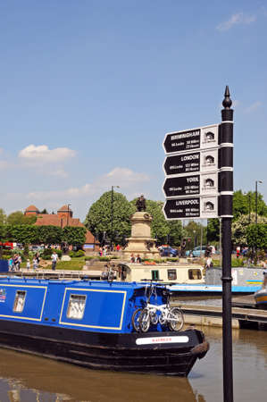 Stratford-upon-Avon, UK - May 18, 2014 - Canal mileage signpost and narrowboat in the canal basin, Stratford-Upon-Avon, Warwickshire, England, United Kingdom, Western Europe