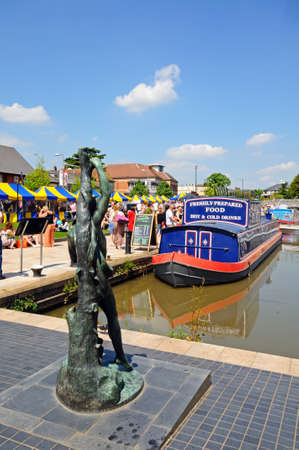 Stratford-upon-Avon, UK - May 18, 2014 - Narrowboat in the canal basin with a statue in the foreground, Stratford-Upon-Avon, Warwickshire, England, United Kingdom, Western Europe