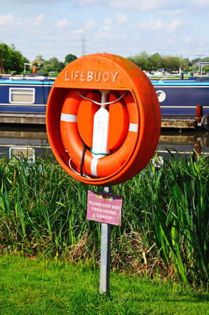 Barton-under-Needwood, UK - May 21, 2014 - Lifebuoy with narrowboats to the rear moored in the canal basin, Barton Marina, Barton-under-Needwood, Staffordshire, England, UK, Western Europe.