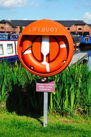 Lifebuoy with narrowboats to the rear moored in the canal basin, Barton Marina, Barton-under-Needwood, Staffordshire, England, UK, Western Europe.