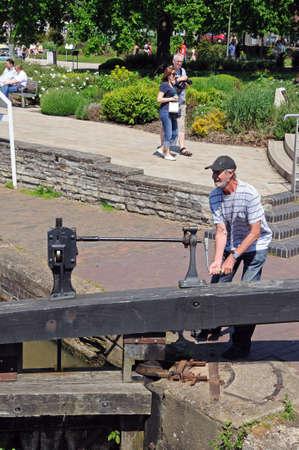 Man opening canal lock gate, Stratford-Upon-Avon, Warwickshire, England, United Kingdom, Western Europe.