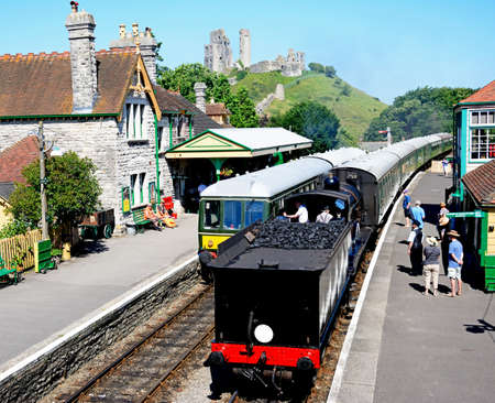 LSWR T9 Class 4-4-0 steam train and BR Class 108 diesel train in the railway station with the castle to the rear, Corfe, Dorset, England, UK, Western Europe.