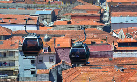 Cable Car Cabins over red roofs of old buildings