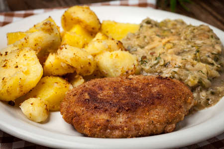 Delicious meal of minced meat cutlet, potatoes and fried cabbage. Selective focus.