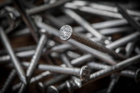 Foto de Steel nails on wooden background. Selective focus. - Imagen libre de derechos