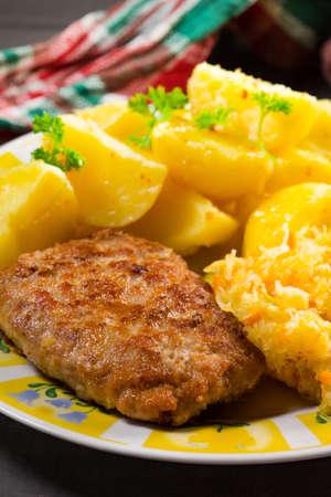 Photo pour Minced pork cutlet served with potatoes and sauerkraut salad. - image libre de droit