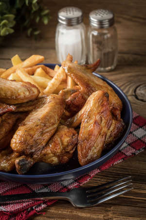 Photo pour Baked chicken wings with french fries on wooden table - image libre de droit