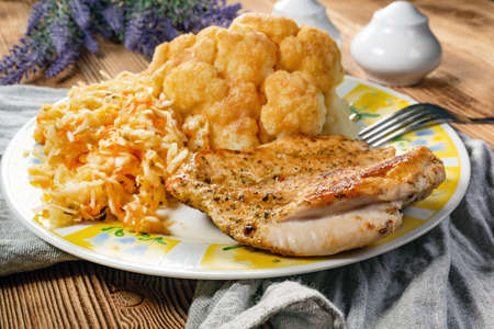 Photo pour Fried chicken breast served with boiled cauliflower and salad. - image libre de droit