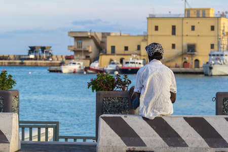 young african immigrant in the port of Agrigento