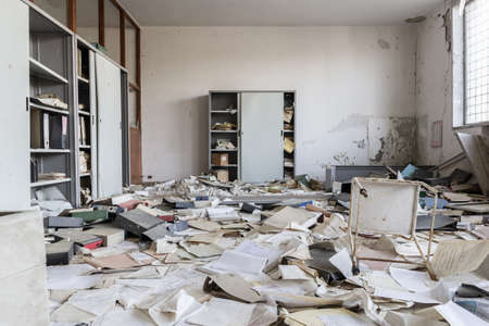 Abandoned office with many papers on the floor