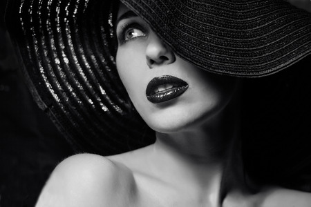 Portrait of mysterious beautiful young woman with wonderful skin texture  in  black hat. Trendy glamorous fashion makeup. Sensual lips. Black and white image. Art photo