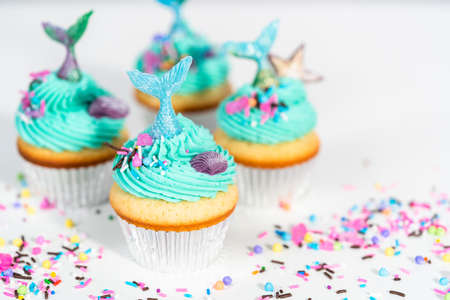 Photo pour Gourmet mermaid cupcakes topped with blue buttercream frosting and decorated with sprinkles and chocolate mermaid tails. - image libre de droit