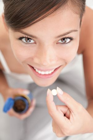 Pills / vitamins woman. Woman taking pills or vitamin tablets.
