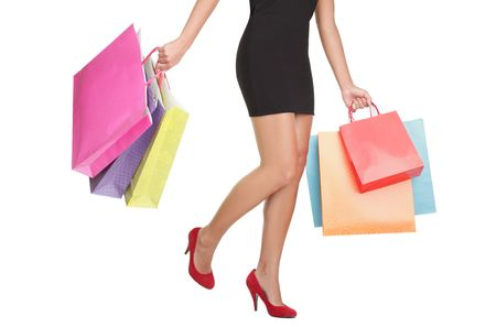 Shopping woman carrying shopping bags. lower half waist down image of sexy legs  in red high heels and colorful shopping bags. Isolated on white background. の写真素材