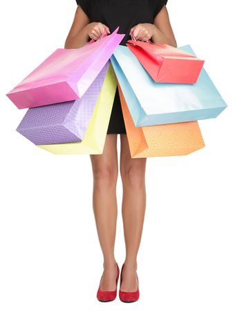 Photo pour Shopping woman holding shopping bags. Closeup of beautiful women legs in red high heels and colorful shopping bags. Isolated on white. - image libre de droit