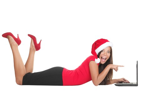 Christmas internet shopping. Woman excited about buying gifts online or winning something on her laptop. Young woman lying down in full length on the floor isolated on white background.