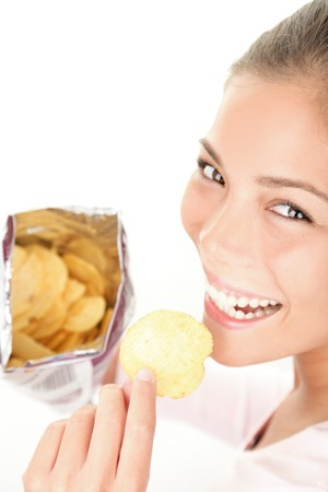 Chips. Woman eating bag of chips / crisps - smiling happy looking at camera. Beautiful young Caucasian / Asian female model.