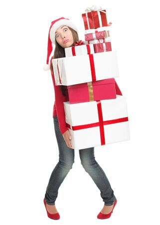 Christmas shopping gifts. Stressed woman with funny expression holding many gift boxes.