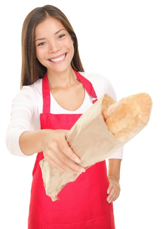 Smiling woman sales clerk giving baguette bread to customer (camera). Isolated on white background.