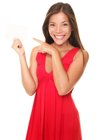 Woman pointing at sign. Young beautiful sexy woman showing copy space on empty blank sign or gift card. Portrait of smiling Asian Chinese / white Caucasian isolated on white background.の写真素材