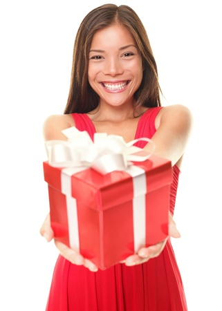 Gift woman in red smiling showing present. Beautiful Asian / Caucasian girl isolated on white background. Shallow depth of field, focus on woman