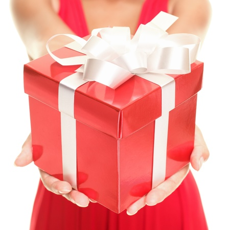 Gift woman showing beautiful red gift box - closeup of present on white background.