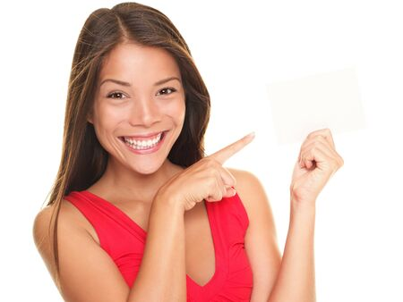 Girl pointing at gift card sign. Young beautiful sexy woman showing copy space on empty blank sign or gift card. Portrait of smiling Asian Chinese / white Caucasian isolated on white background.
