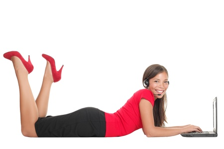 Woman with laptop computer talking in headset lying down on the floor. Isolated on full length on white background.