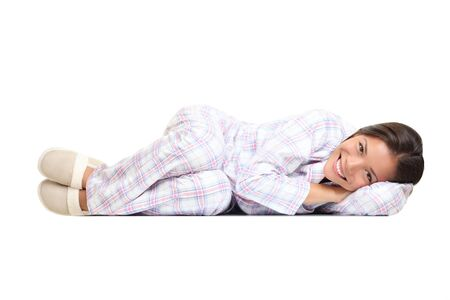 Woman lying down cute in pajamas and slippers. Isolated on white background.