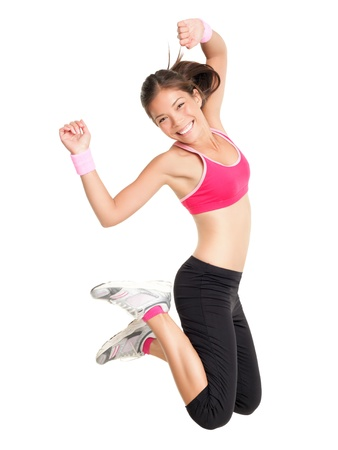 Foto de Weight loss fitness woman jumping of joy. Young sporty fit mixed race Asian / Caucasian female model isolated on white background in full body - Imagen libre de derechos