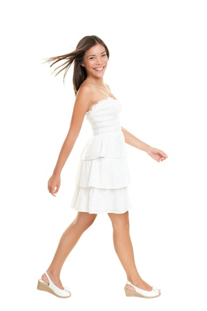 Woman in white dress walking isolated on white in full length.  Beautiful fresh smiling young mixed race Asian Caucasian female model in cute summer dress.