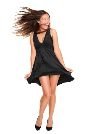 Playful funny woman excited standing in black dress. Beautiful happy mixed race Asian Caucasian model isolated on white background in full body.