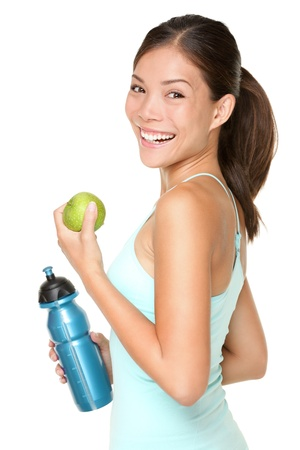 Foto de Fitness woman happy smiling holding apple and water bottle. Healthy lifestyle photo of Asian Caucasian fitness model isolated on white background. - Imagen libre de derechos