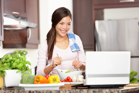 Cooking woman looking at computer while preparing food in kitchen. Beautiful young multiracial woman reading cooking recipe or watching show while making salad.