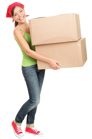 Woman carrying moving boxes. Young woman moving house to new home holding cardboard boxes isolated on white background standing in full length.