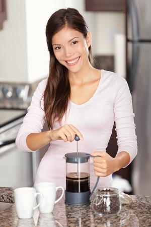 woman making coffee in kitchen - french press coffee. Mixed race Asian Caucasian female model in her twenties at home.