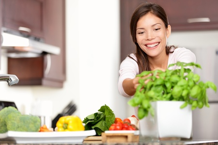 Woman Making Food In Kitchen Reaching For Basil Plant