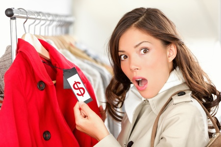 Foto de shopping woman shocked and surprised over price looking at price tag on coat or jacket. Woman shopper shopping for clothes inside in clothing store. Funny image of Asian / Caucasian female model. - Imagen libre de derechos