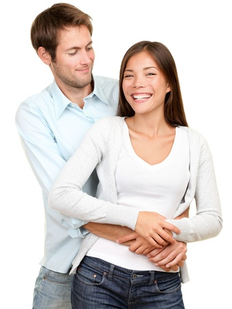 young couple smiling happy. Interracial couple, Asian woman, Caucasian man isolated on white background.