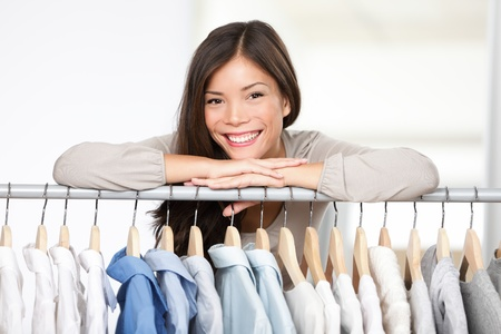 Photo pour Business owner - clothes store. Young female business owner in her shop behind clothes rack smiling proud and happy. Multicultural Caucasian / Asian female model. - image libre de droit